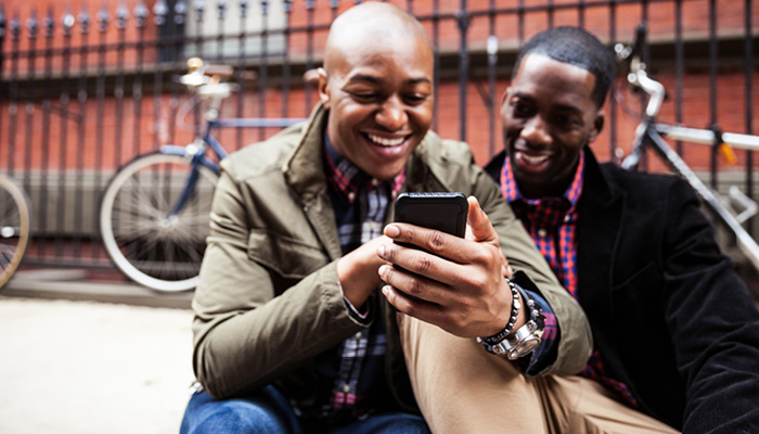 Happy homosexual couple using mobile device