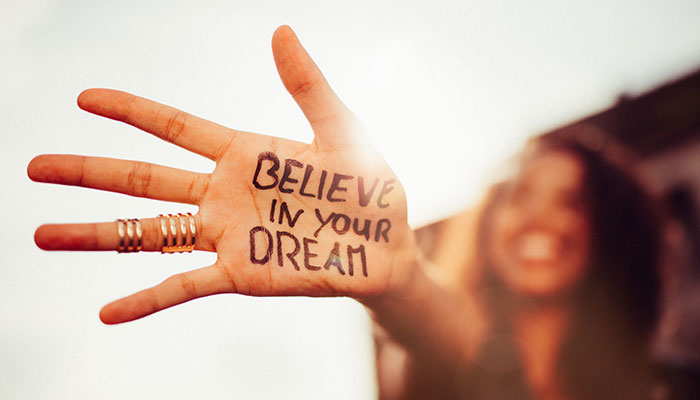 "Girl with ""believe in your dream"" written on her hand"