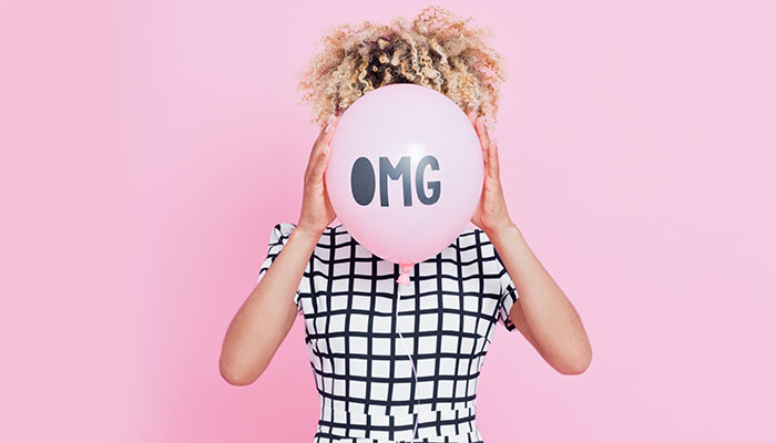 "Girl holding a balloon reading ""OMG"""