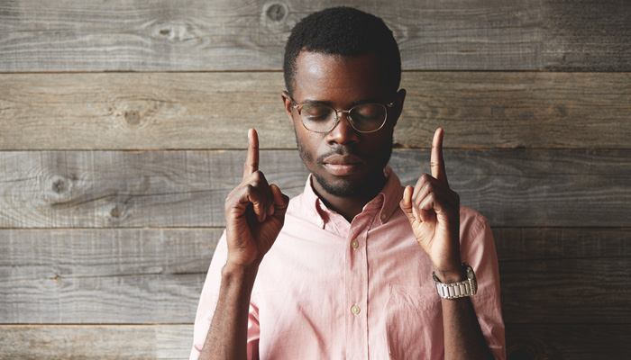 african american male with eyes closed and pointing fingers upward