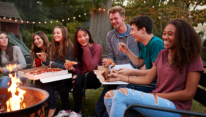 happy group of friends eating pizza outside