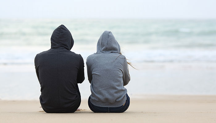 Two people sitting on the beach