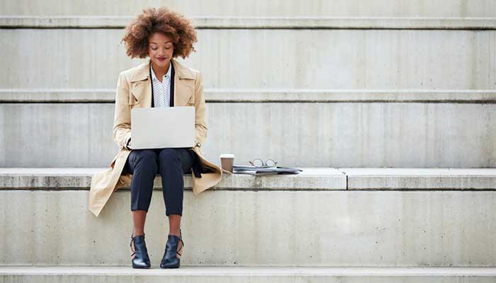 young businesswoman using laptop on stairs