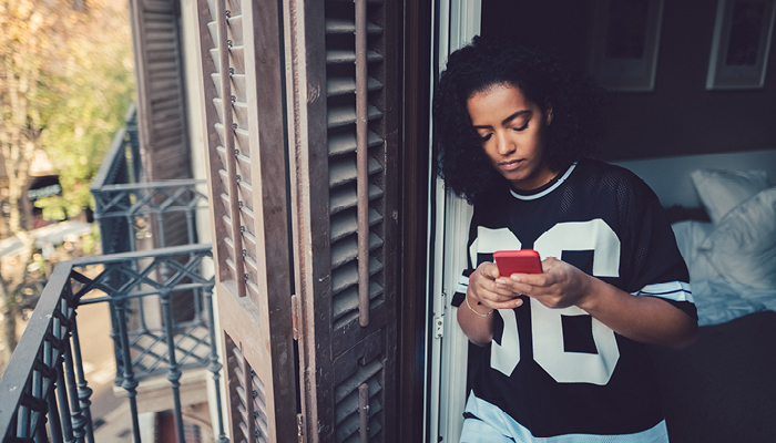 worried african american young woman looking at phone