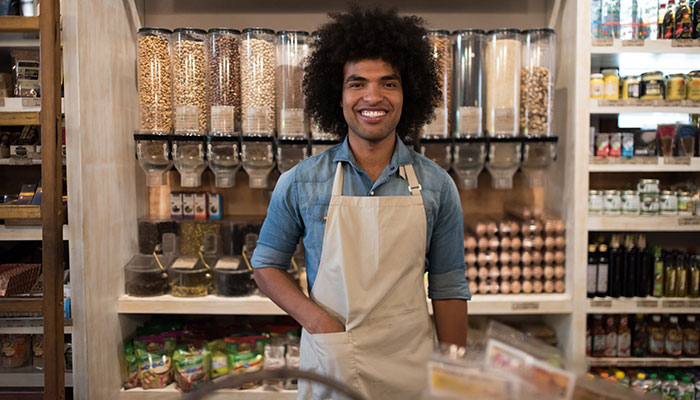 Male retail employee smiling