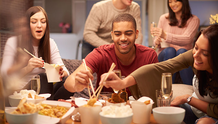 Group of young adults sharing Chinese takeout