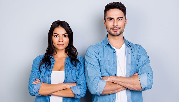 girl and guy standing next to each other with arms crossed