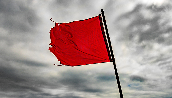 tattered red flag in stormy sky | when does drinking become a problem