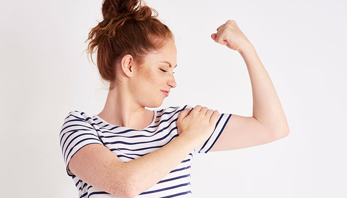 young woman flexing arm
