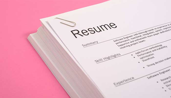stack of resumes on pink background