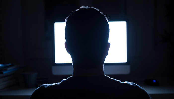 rear view of person sitting in front of computer screen with blue light