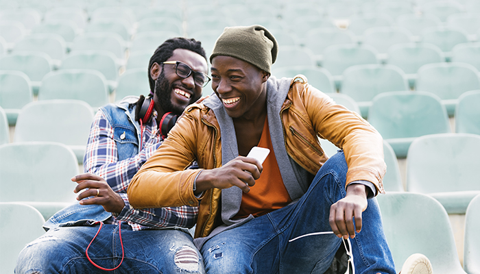 two Black male friends chatting and laughing | tips for managing anxiety