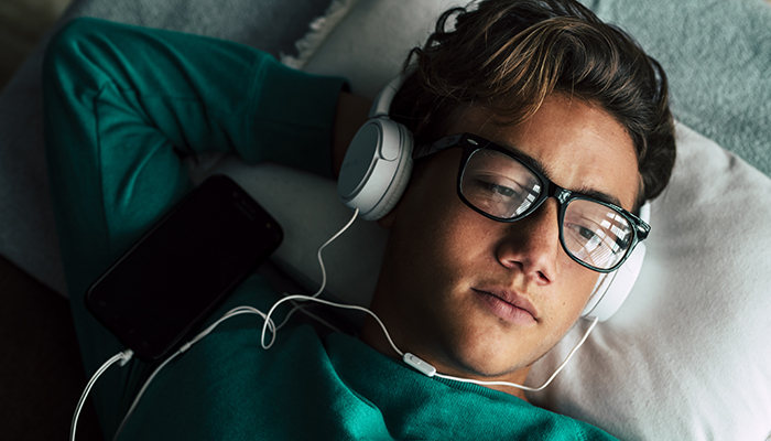 pensive young man wearing headphones and laying down | tips for managing anxiety