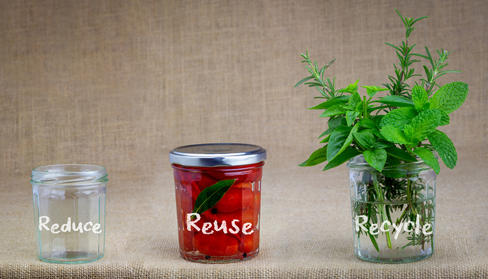 """three glass jars labeled """"reduce"""", """"reuse"""", and """"recycle"""" 