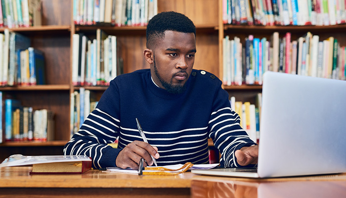 guy looking at computer in library
