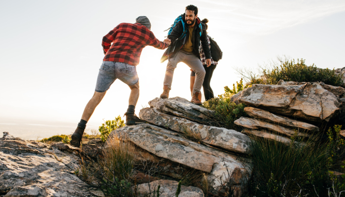friends helping each other on hike