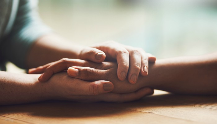 closeup of holding hands, suicide prevention concept