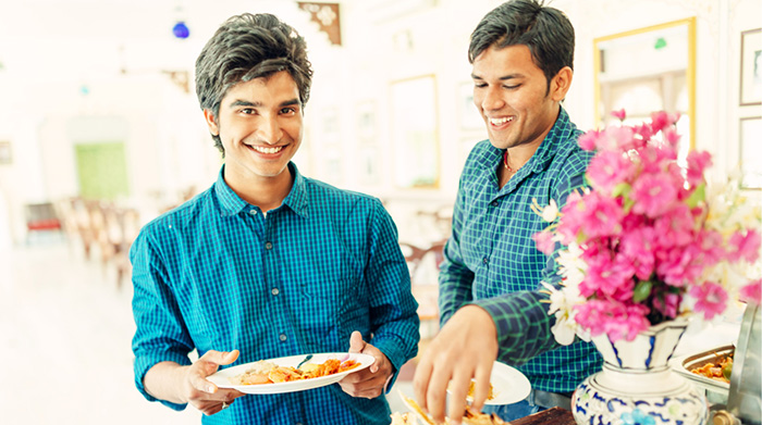 Two young men preparing plates of food