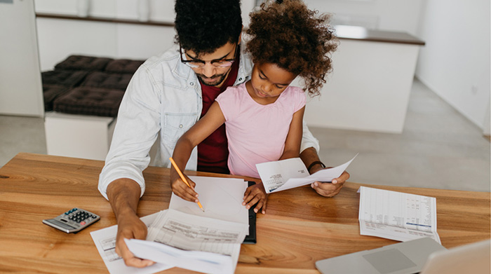 Father balancing finances with young girl on lap