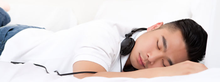 Young asian male napping with headphones on neck