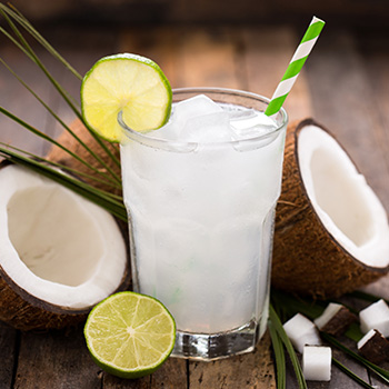 a glass of coconut water with coconuts and limes next to it