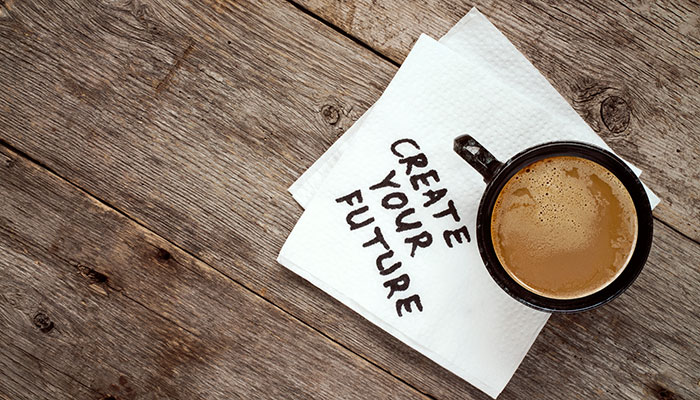 "Cup of coffee with napkin saying ""Create your future"""