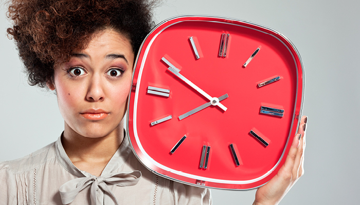 African American young woman holding giant clock
