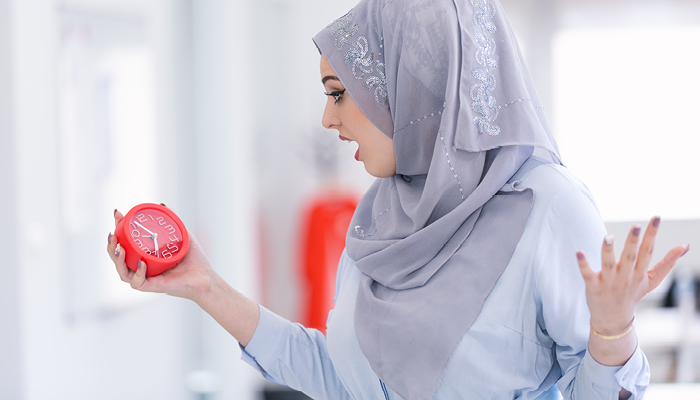 Surprised Middle-Eastern female looking at clock