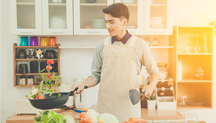 Young asian male cooking in kitchen
