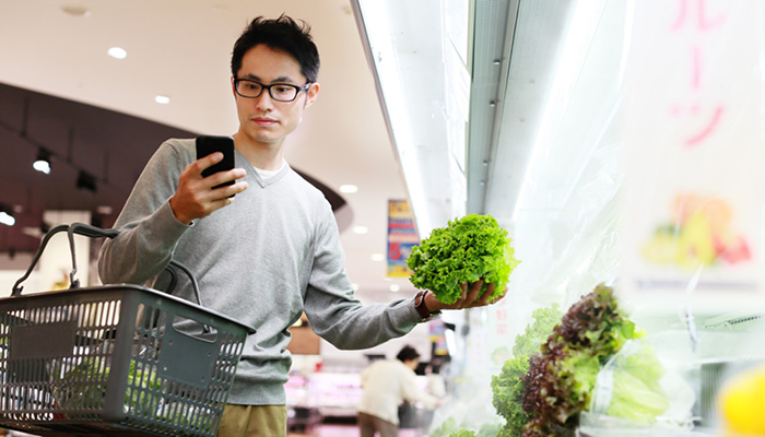 Asian male food shopping for vegetables