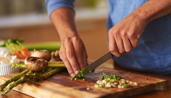 Close up of hands chopping vegetables