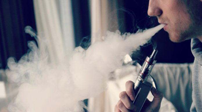 Man is pictured blowing out smoke while holding a vape.