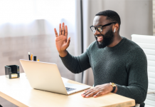 Man waving to others on a virtual meeting/presentation