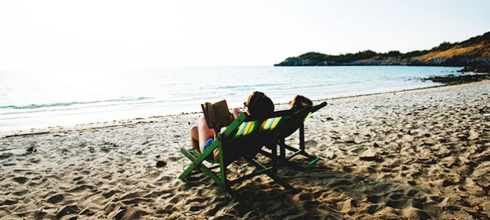 Two females reading on the beach