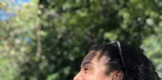 A picture in side profile of the author, Jade Diouf, a woman with dark curly hair. She has sunglasses on her head. She is smiling and the sun is shining on her face.