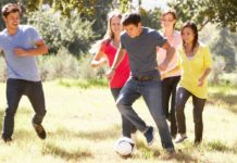 College students playing soccer outside