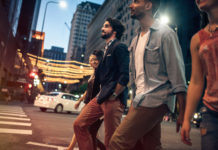 A group of multi-ethnic young adults explore and walk around downtown Los Angeles, California on a summer evening, checking out the city night life. They walk casually down a city street lined with cars and tall buildings, talking and enjoying the night.