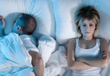 A couple in bed where one is unable to sleep