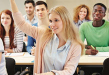 Young woman raising her hand in class