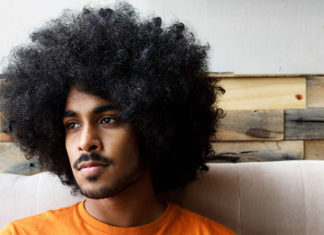 Young man with an afro looking off to the right
