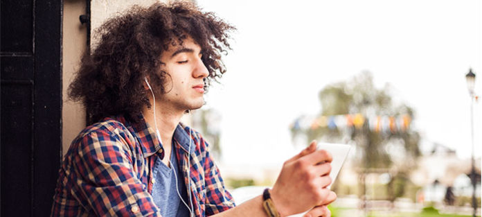 Young man listening to music on tablet