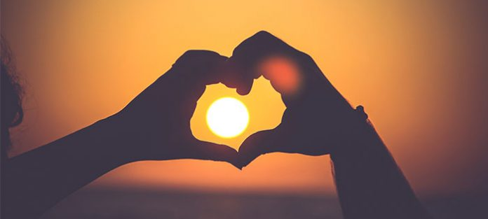 Hands-making-a-heart-in-a-sunset