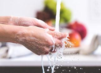 Person-washing-their-hands-in-a-kitchen-sink