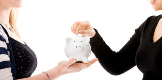 Two-female-students-saving-money-in-a-piggy-bank