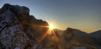 Image of the sun coming through the rocks in the Rocky Mountains.