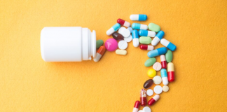 Bottle with pills spilling out into question mark