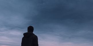 silhouette of man standing in front of sunset