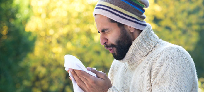 Young man sneezing into a tissue