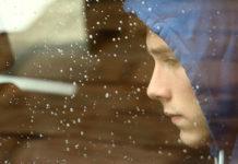 Sad boy looking out rainy car window