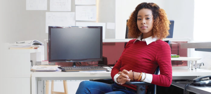 Confident woman sitting at her computer desk